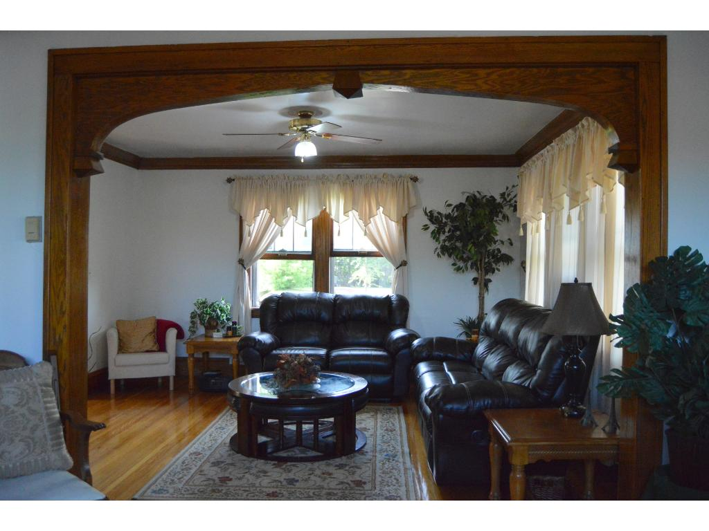 Living room with hardwood floors, crown molding, and wood trim