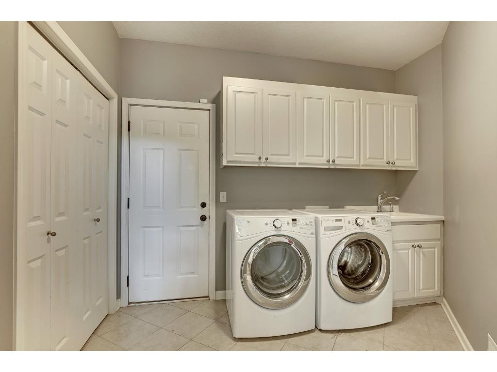 Off the kitchen, next to the desk area, is the laundry room and access to the over-sized three car garage