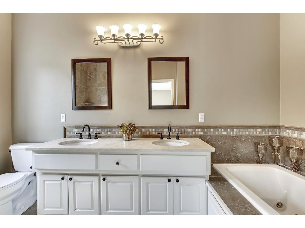 Updated master bath with separate shower, dual sinks, higher-than-standard counter height and inviting tub