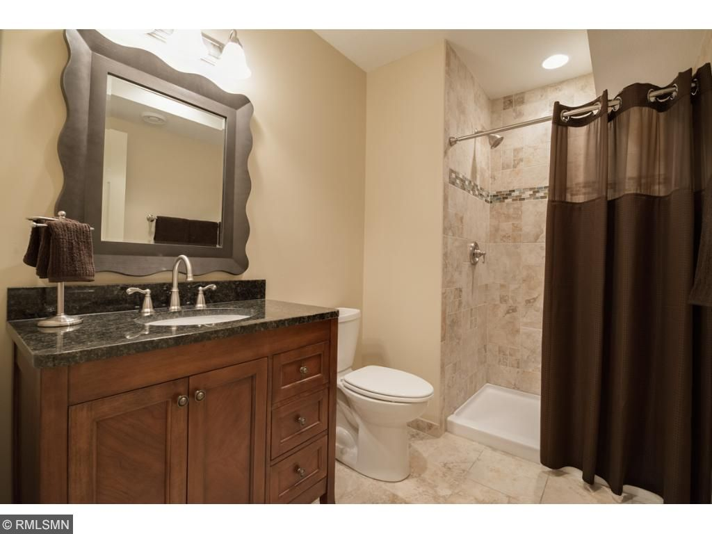 Expertly finished 3/4 lower level bath with artistic ceramic tile shower surround and floor, vanity with granite top and unique picture-frame mirror.