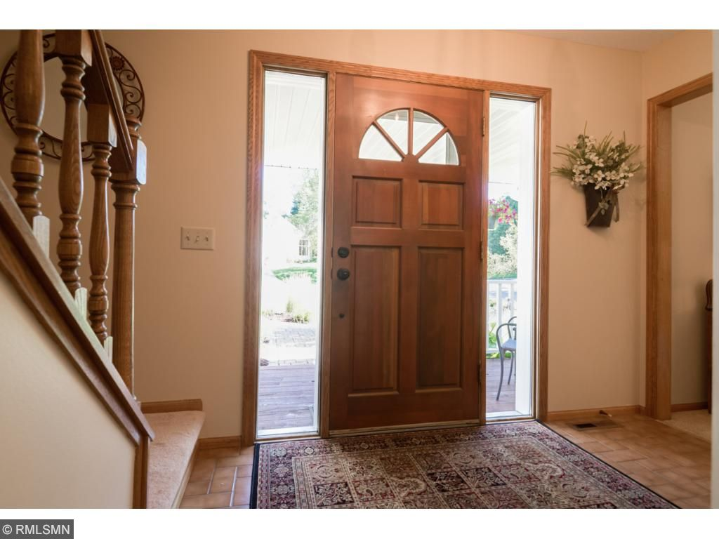 Heavy wood front door with ellipse window and double sidelights lead you into the front foyer with easy-maintenance ceramic tile floors.