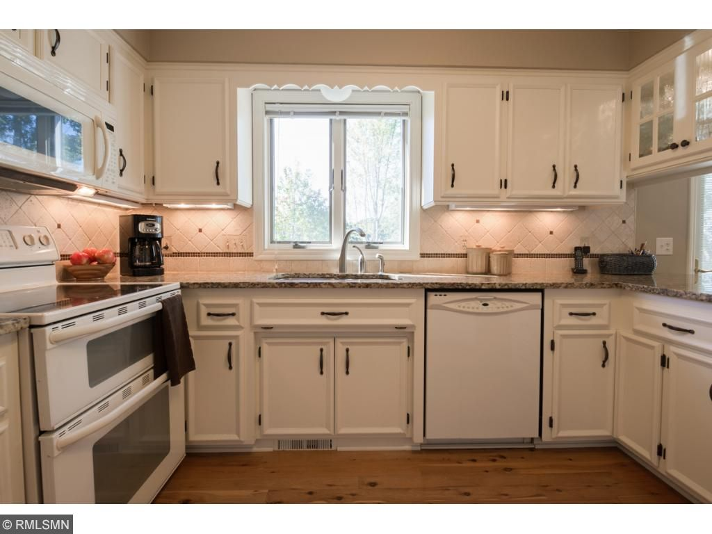 Gorgeous remodeled kitchen boasts granite counters, professionally enameled cabinets, beautiful white appliances including stove with double oven and built in microwave.  Great counter space for food prep!