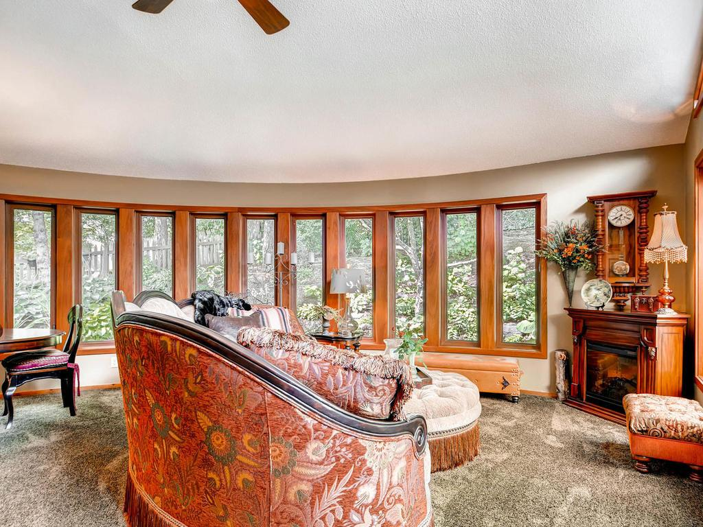The one-of-a-kind four season porch room features picturesque views from the curved wall of glass is and perfect for additional entertaining and access to the gorgeous outdoor living area.