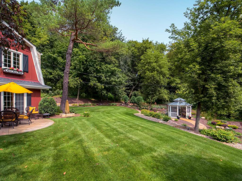 You may just feel like you're in your own private park!  The lot is almost an acre and is professionally designed and landscaped with beautiful plants and green space.  The home is surrounded by mature trees.