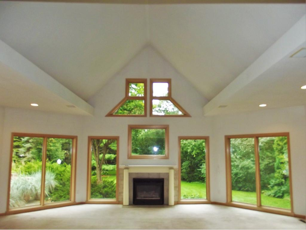 Great room is highlighted by vaulted ceiling, gas fireplace and expansive views of the yard.