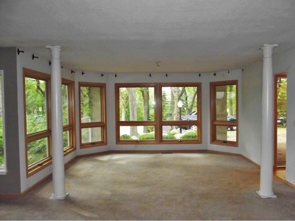Living room surrounds you with windows overlooking the front yard.