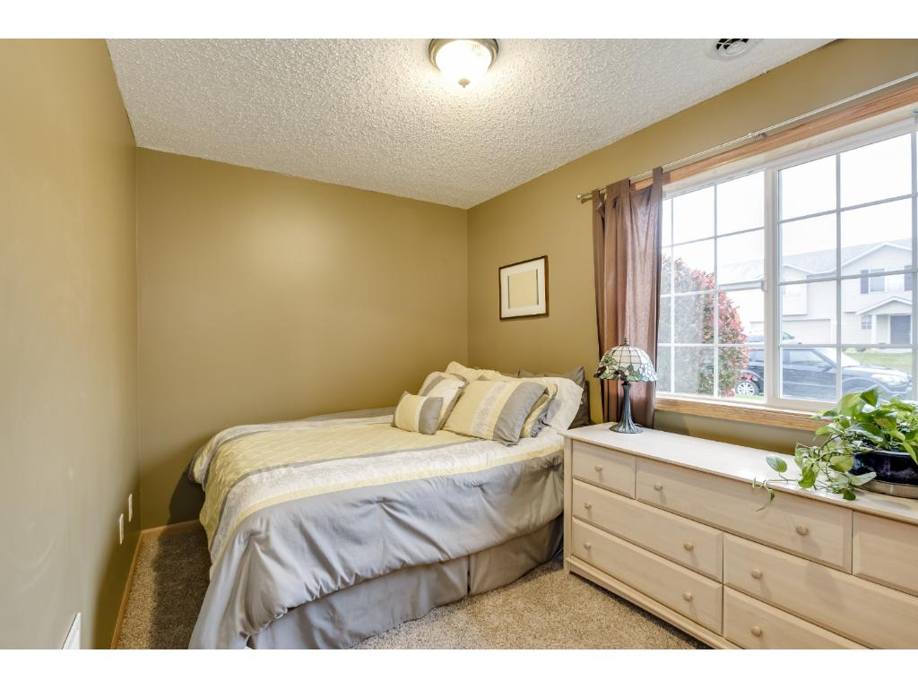 The lower level bedroom has neutral dcor and a bright south-facing window.