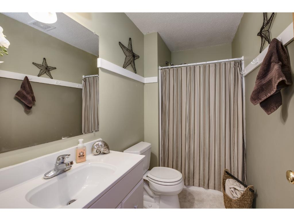 The lower level 3/4 bathroom is updated with neutral paint and flooring and a white vanity.