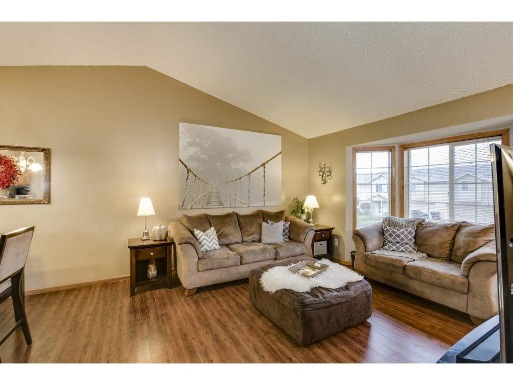 The main/upper level family room has a vaulted ceiling, hardwood-style flooring, and bright windows.  You'll love the neutral, warm decor.