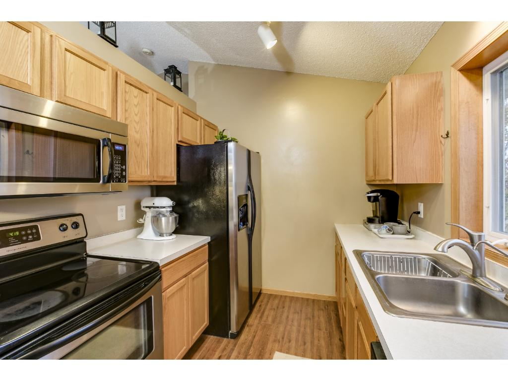 The kitchen has stainless steel appliances, a bright window, and updated flooring.