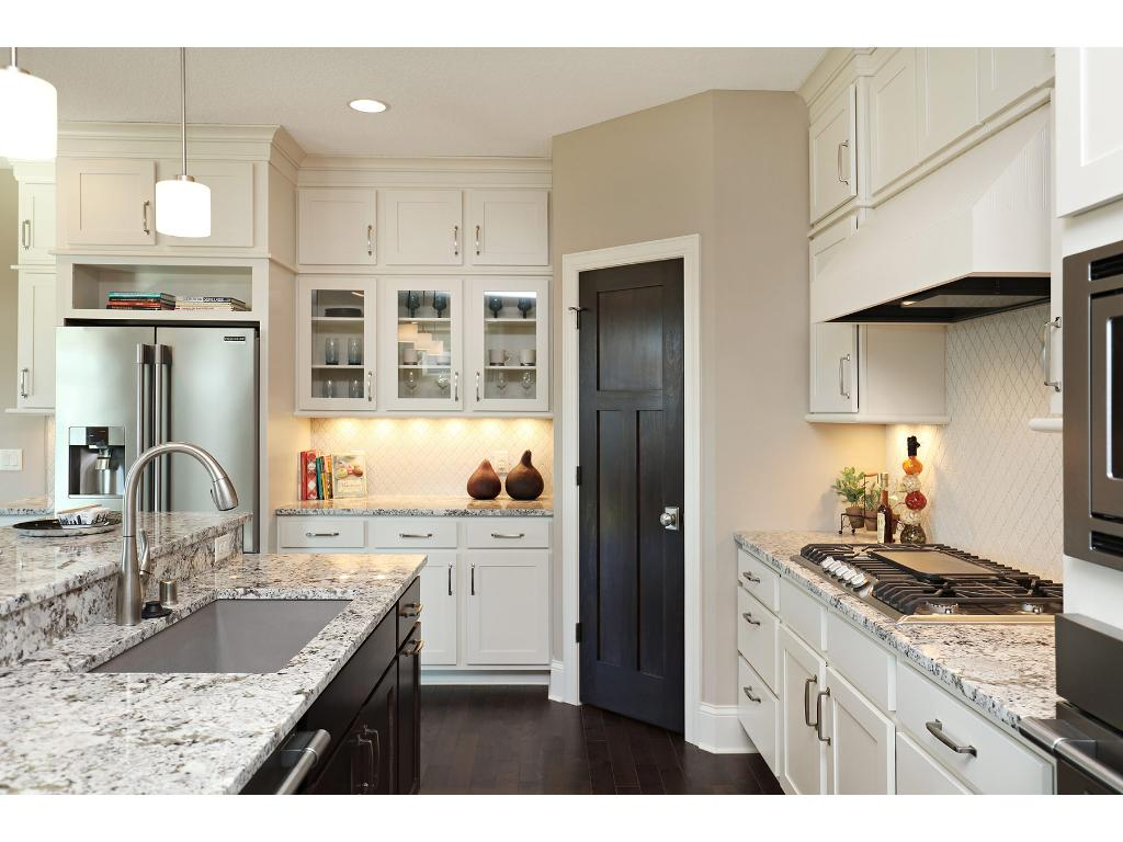 This Gourmet Kitchen features enameled glass front cabinetry