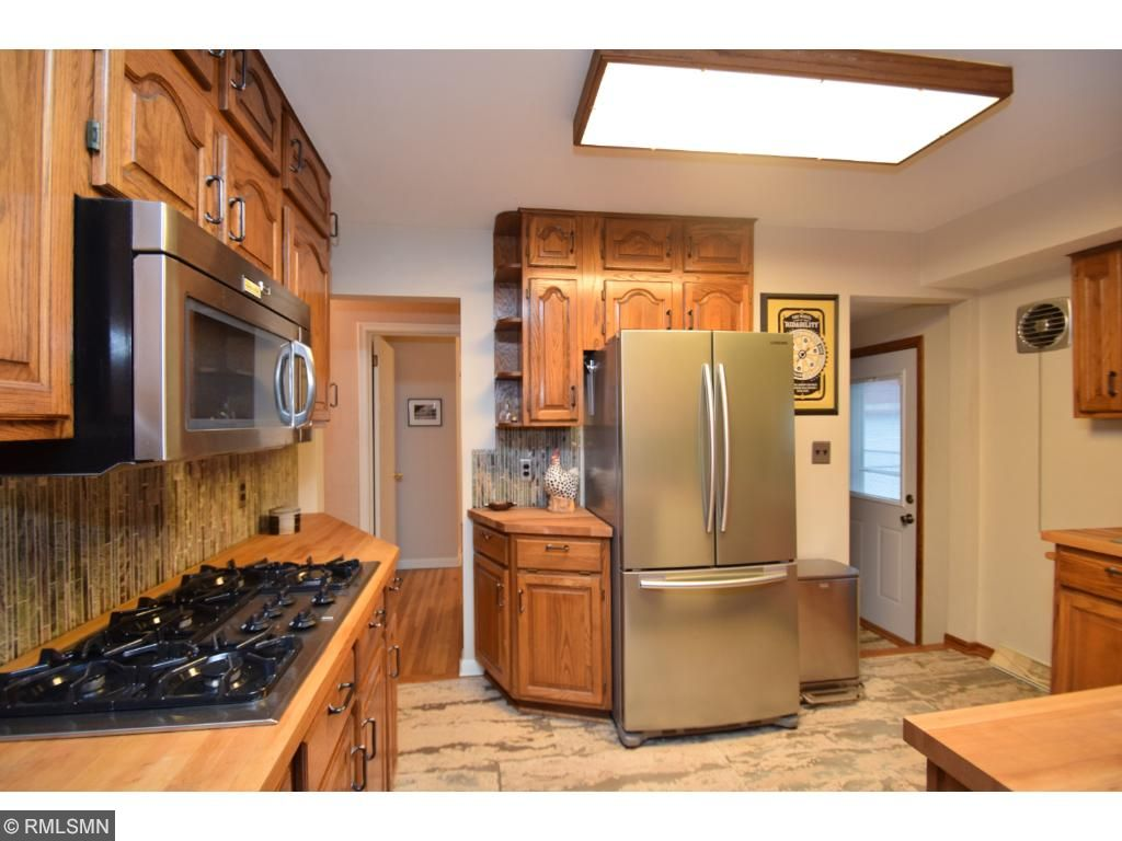 Kitchen, cork flooring, maple cutting board counter tops, marble back splash, SS double oven, 5 burner gas stove, microwave and refrigerator.