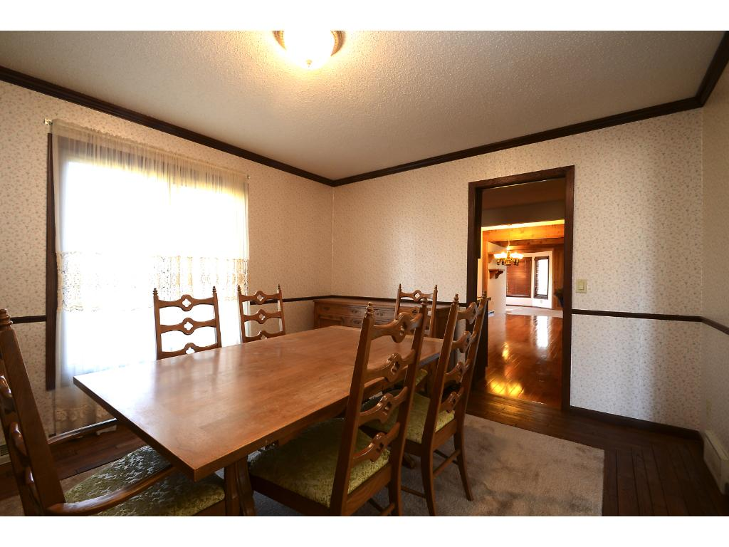 Dining room has outer wood floor and carpet in the interior section of the room