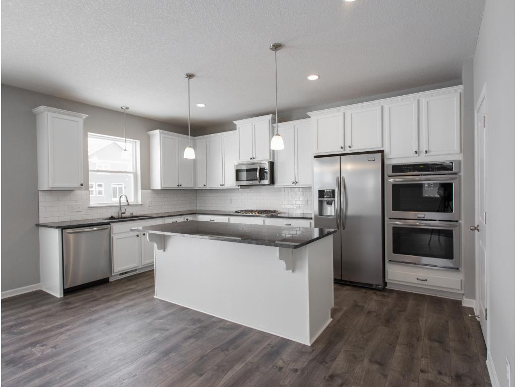 White maple cabinetry, granite counter tops, subway tile back splash,single basin under-mount sink, kitchen window, eat at center island, spacious pantry and much more!