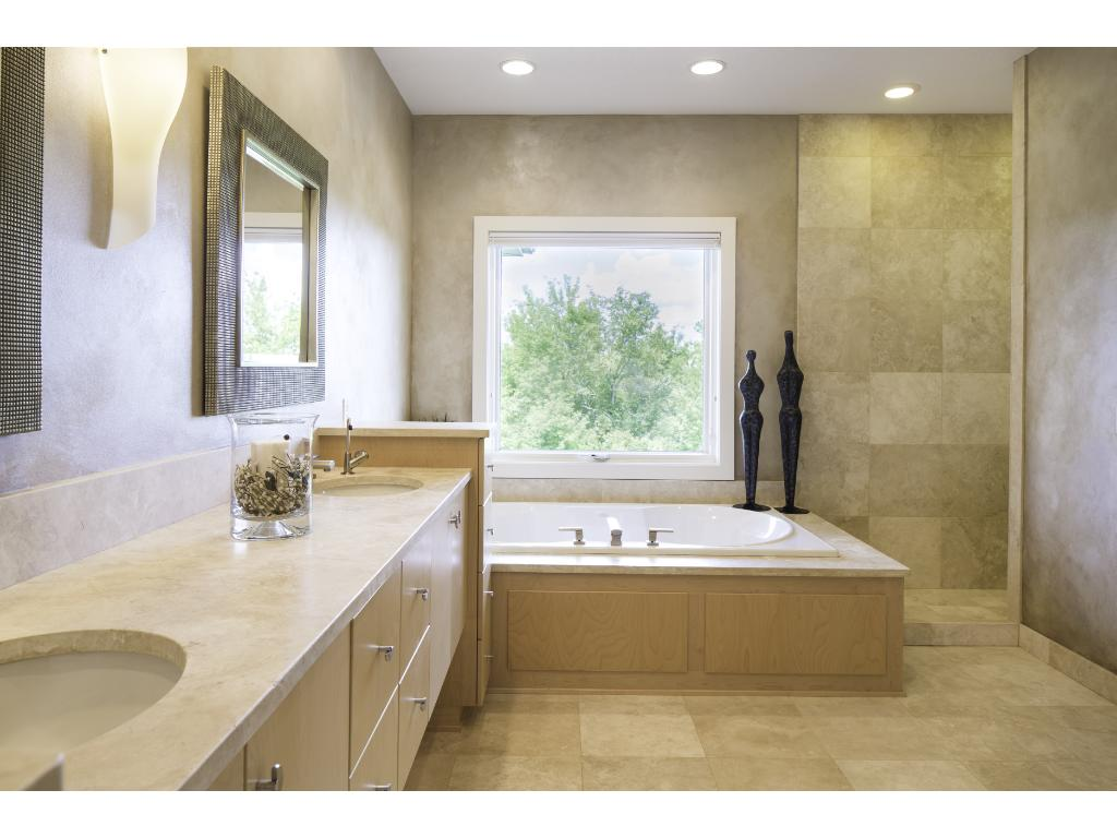 Retreat to the extravagant master bath featuring luxurious soaker tub, soothing accent lighting, dual vanities, walk-in multi-spray shower, separate commode area & heated flrs! Enormous walk-in closet is equipped w/ custom shelving & built-in bureau.