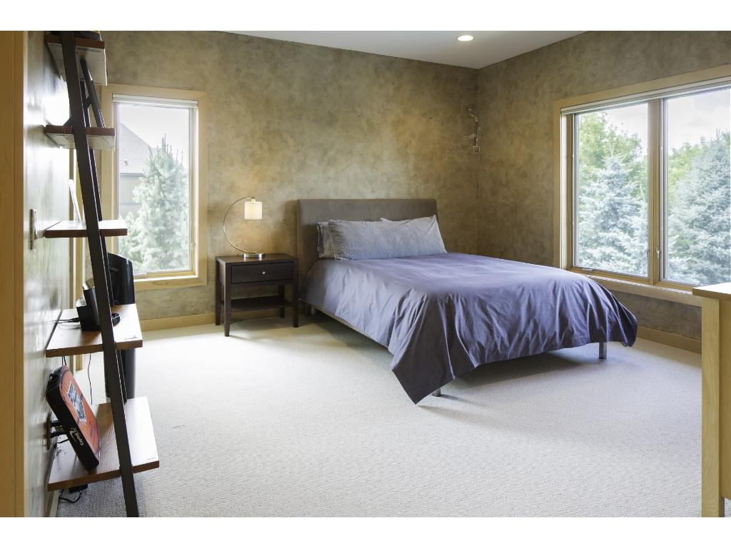 View of one of the two additional junior bedrooms  located on the upper level offering a private 3/4 bathroom and walk-in closets with custom organizers.