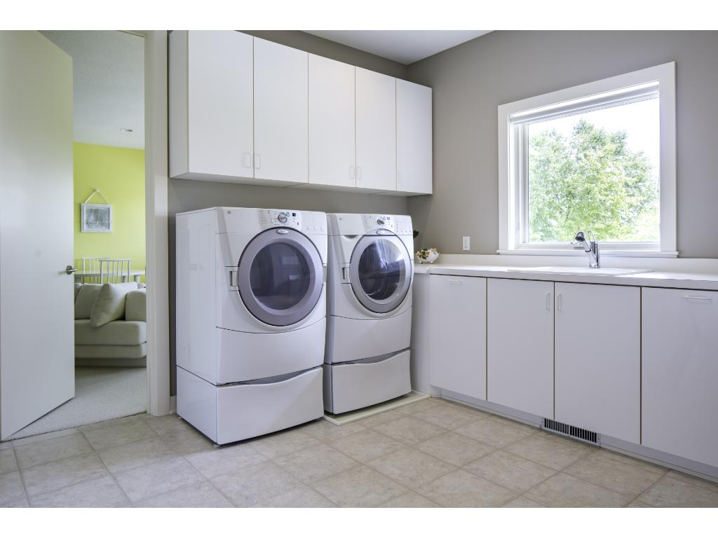 Convenient upper level laundry room. Also in view is the large bonus room providing a perfectly secluded area for a 2nd office or craft room. Highlights include a wall of cabinets for all your storage needs & large sun-filled windows.