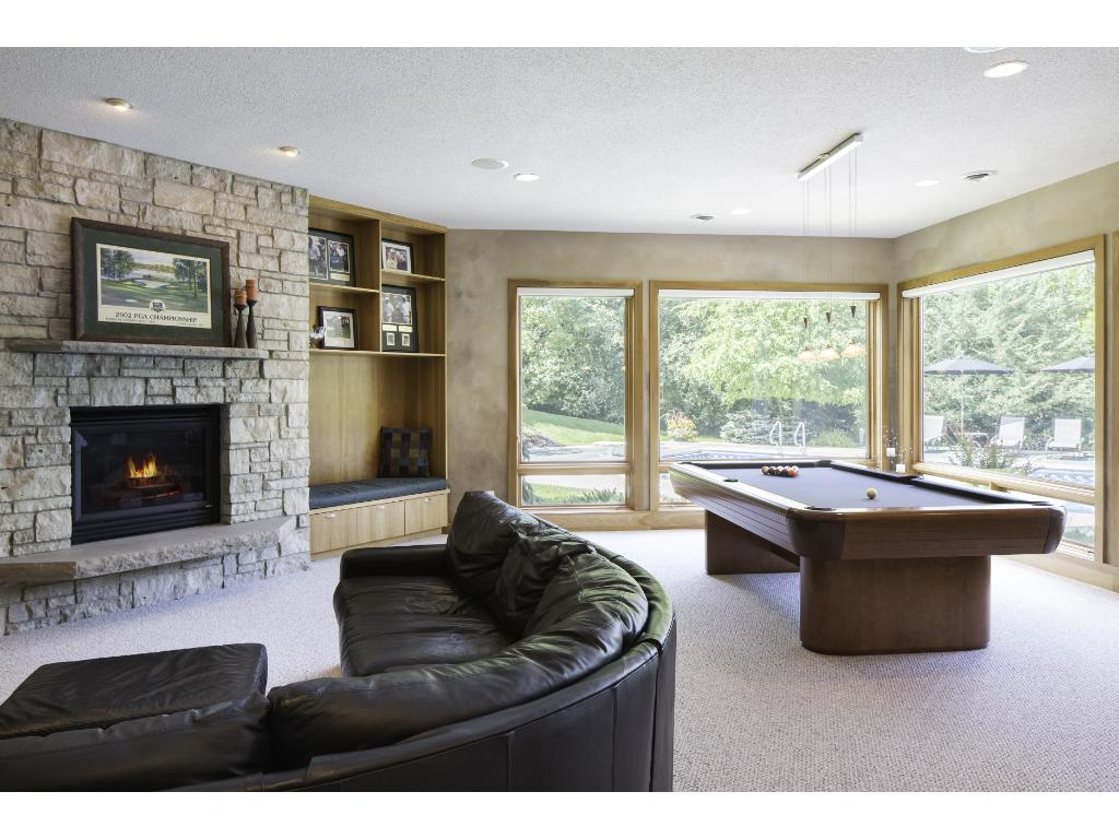 Spacious lower level family room features a beautiful stone fireplace and built-ins! Enjoy a friendly game of billiards or sit down to a hand of cards w/ friends & family! In-floor heat can be found thru-out the home.