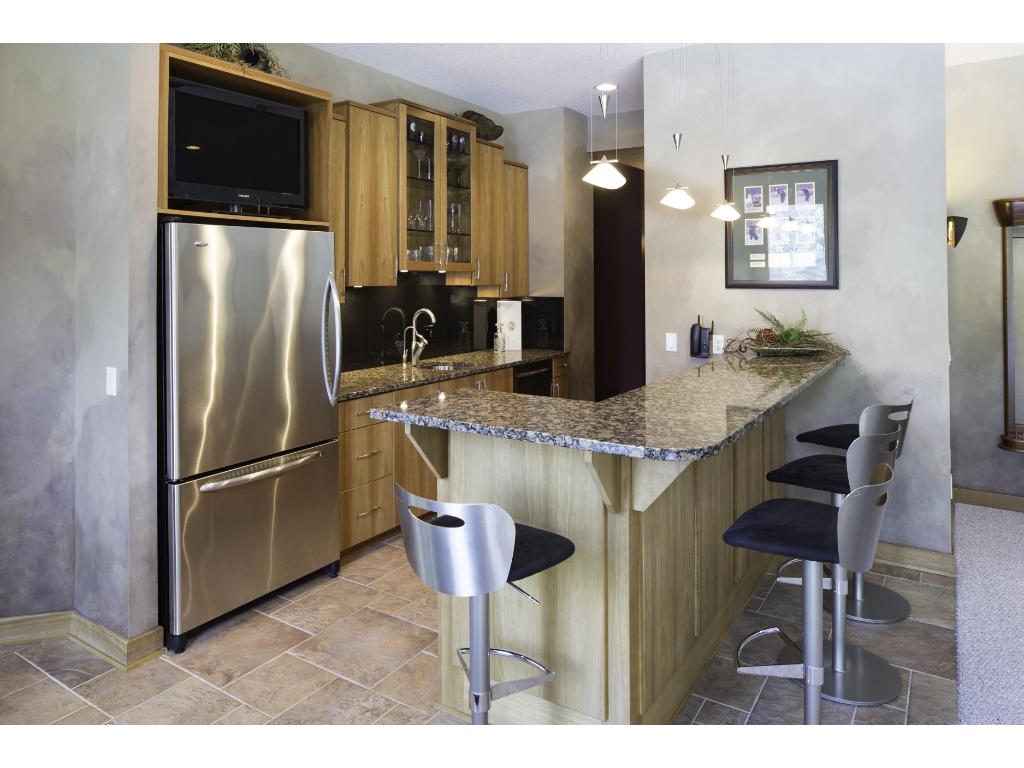 Remarkable wet bar features a full suite of stainless steel appliances, many custom cabinets & beautiful granite-topped bar!
