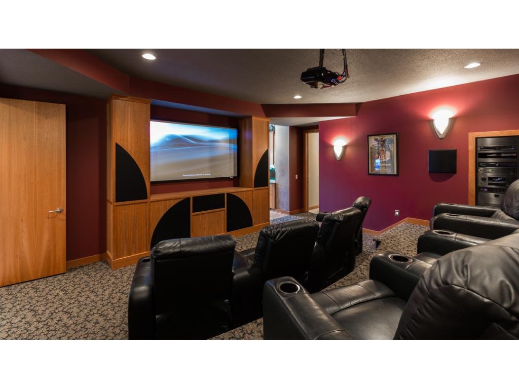 Enjoy favorite movies & TV shows in the comfort of your own in-home theater! Details including stadium seating for 8 people, attractive wall sconces w/ dimmers & overhead theater projector w/ built-in surround sound!