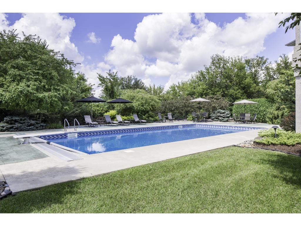 Walk out to the fabulous stamped concrete terrace w/ 47' heated pool! Pool offers diving board, new liner & auto cover! Plenty of space for lounging around the pool & basking in the sun. Nearby fire pit is nicely appointed with stone seating.