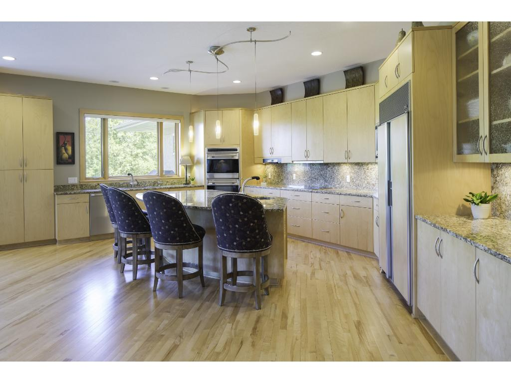 Spacious gourmet kitchen features sparkling granite countertops, deluxe Wolf appliances incl a new induction cooktop & Sub-Zero fridge, large walk-in pantry & an expansive center island that offers the perfect gathering place for friends & family!