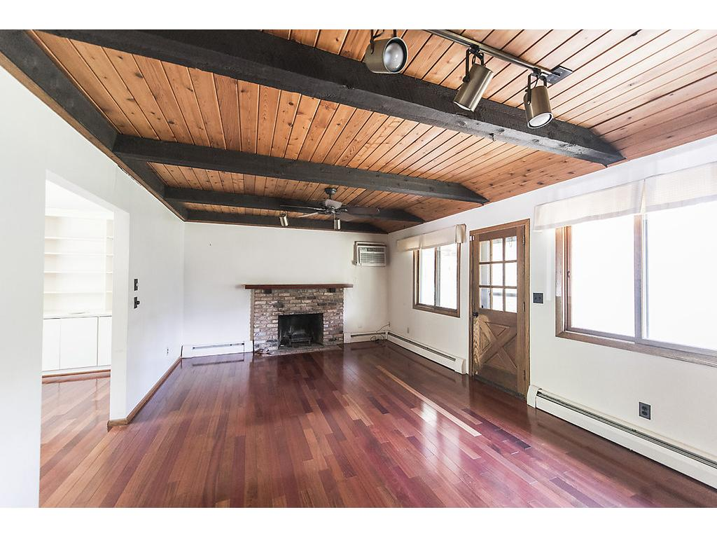 Hardwood floors, custom beamed ceiling with original woodwork, loads of windows, brick fireplace, professionally cleaned and so much more to see!