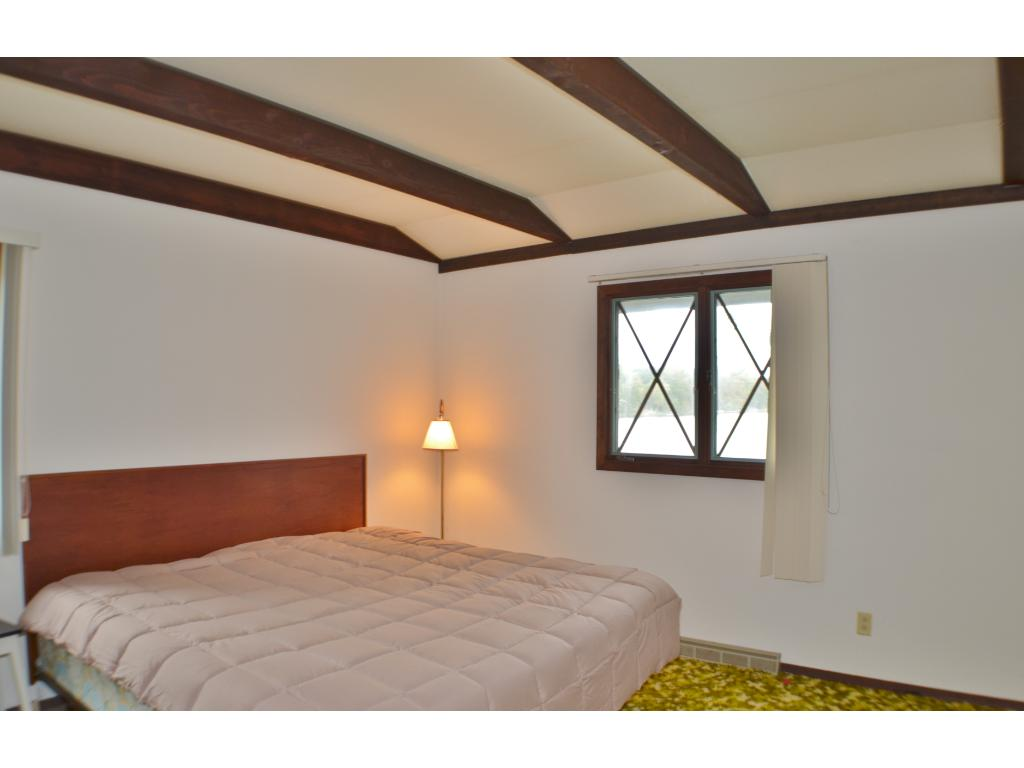 The master bedroom on the main floor continues with the dark exposed wood beams and large window for beautiful views!