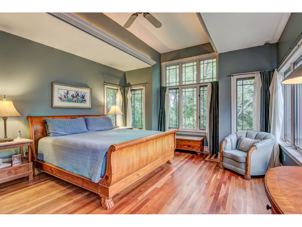 A luxurious place to end and greet the day ~ the main floor owner's suite has beautiful morning light and opens to its own deck overlooking the gardens and pool.