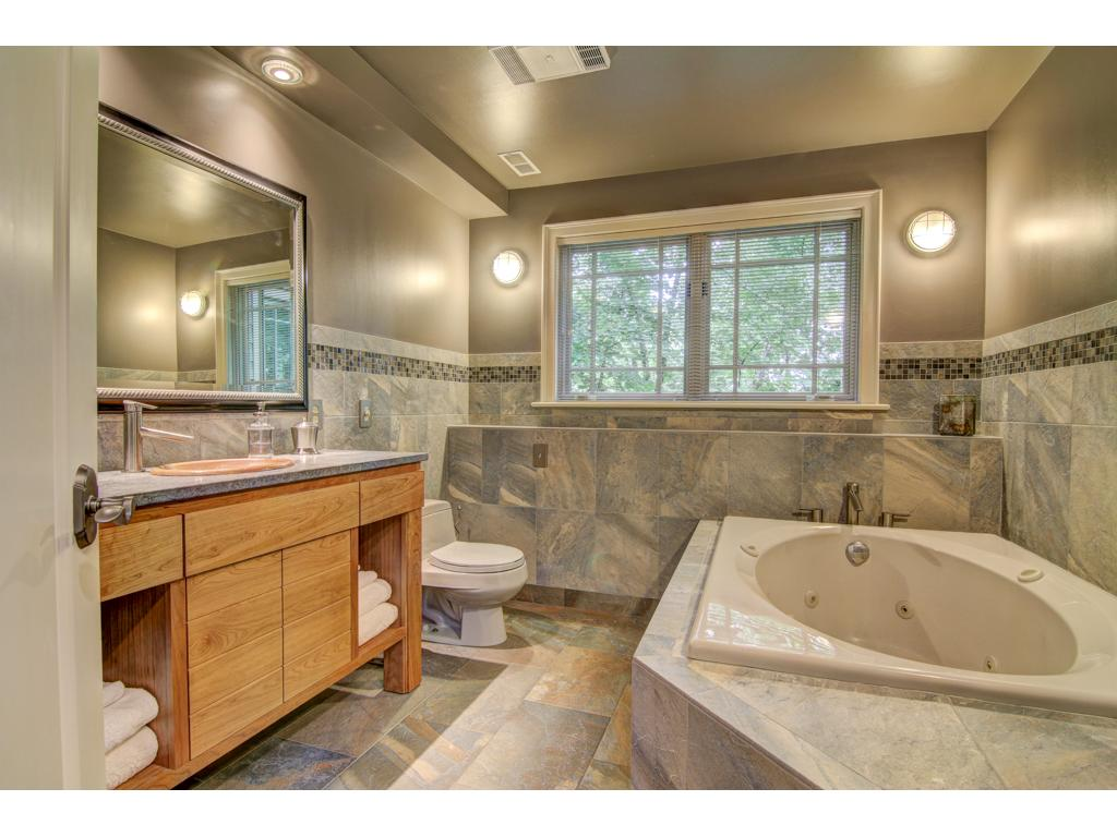 The 2nd lower level bath has a separate glass and tile shower and jetted tub.