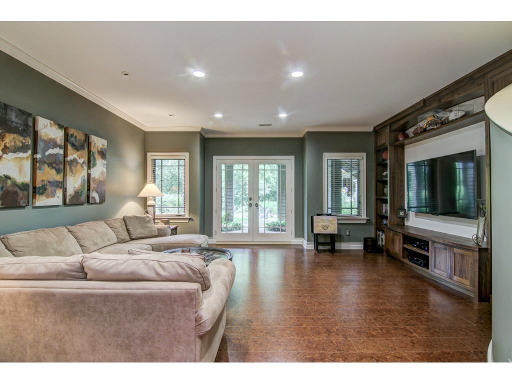 Lower level family room where you'll enjoy bringing the gang in for those Sunday afternoon football games! French doors open onto the patio surrounded by lovely gardens.
