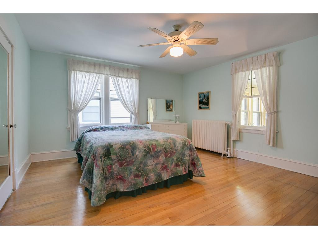 Spacious upper levels second bedroom also featuring a ceiling fan and hardwood floors!