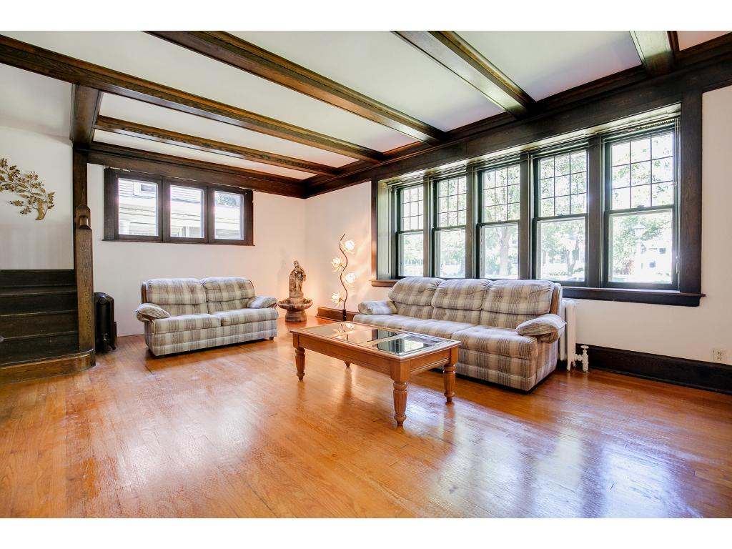 Beautiful main floor living room features gorgeous beamed ceilings and gleaming hardwood floors!
