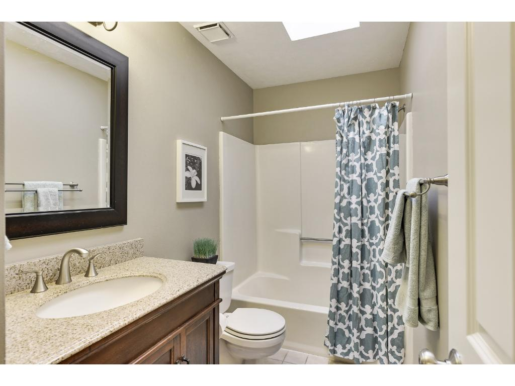 Updated Main Floor Full Bathroom with Granite Counters, new Vanity and Sink, new Light fixture, new Faucet, and Skylight!
