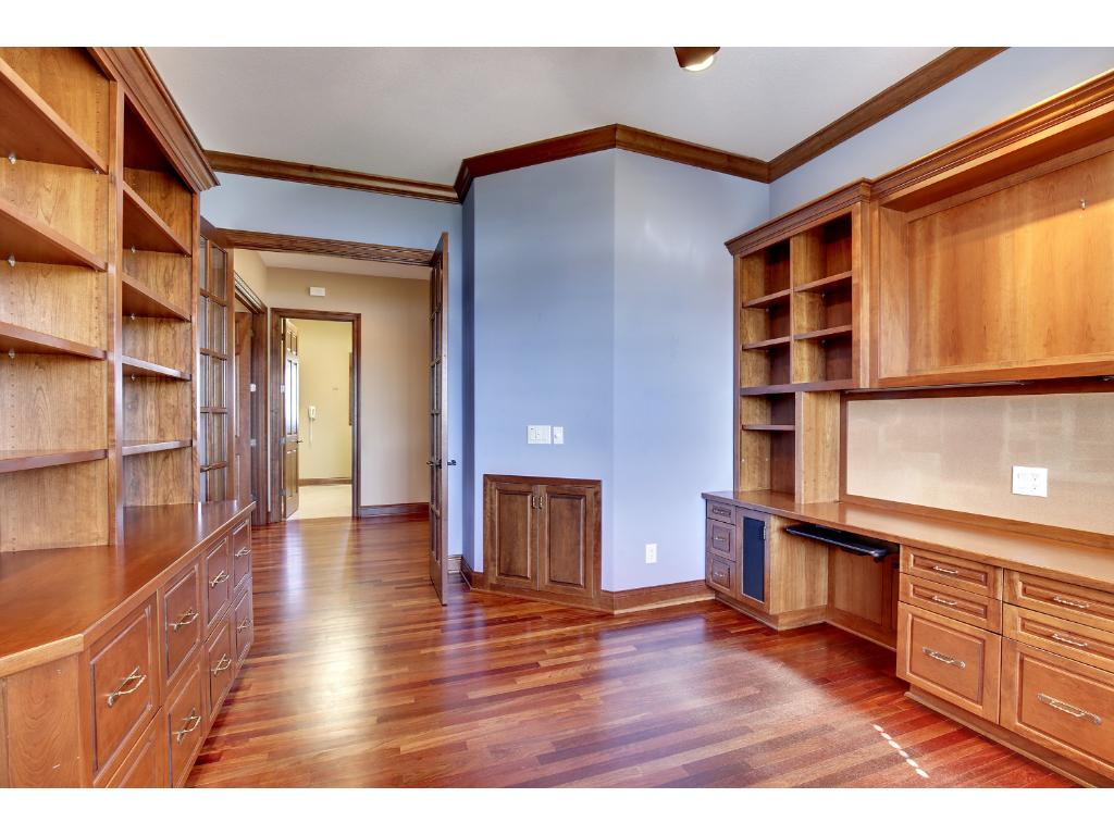 Main floor office with Brazilian cherry floor, built-in desk and extensive book shelves and cabinets.