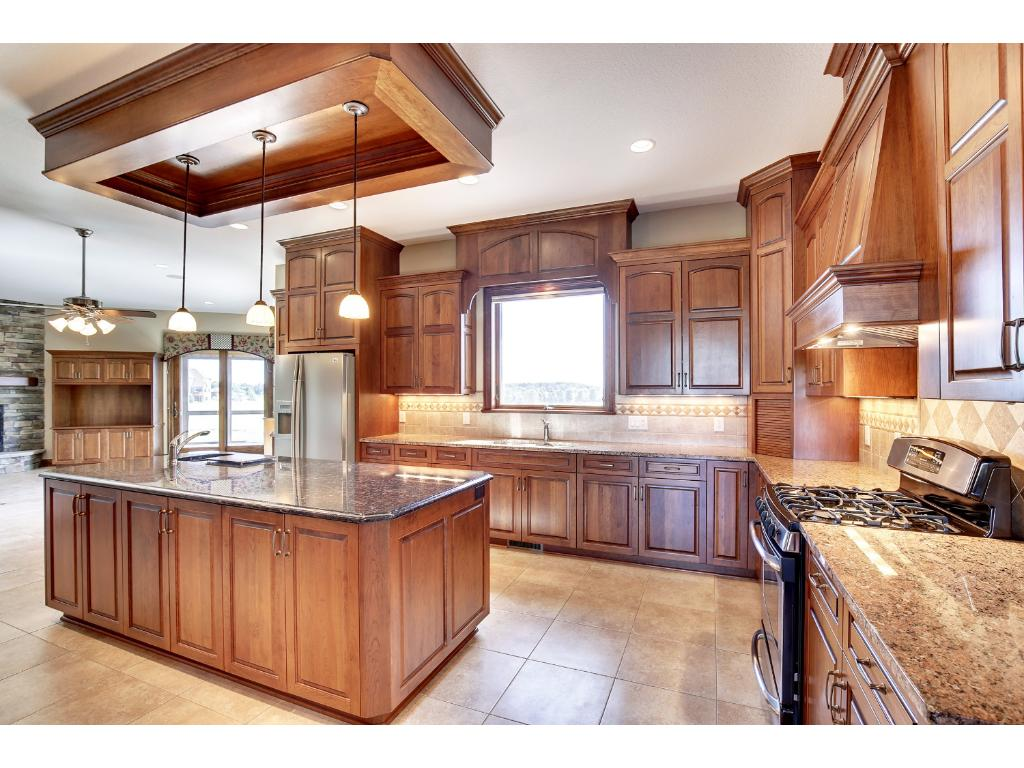 Gourmet kitchen with granite counters, stainless steel appliances and heated floors.