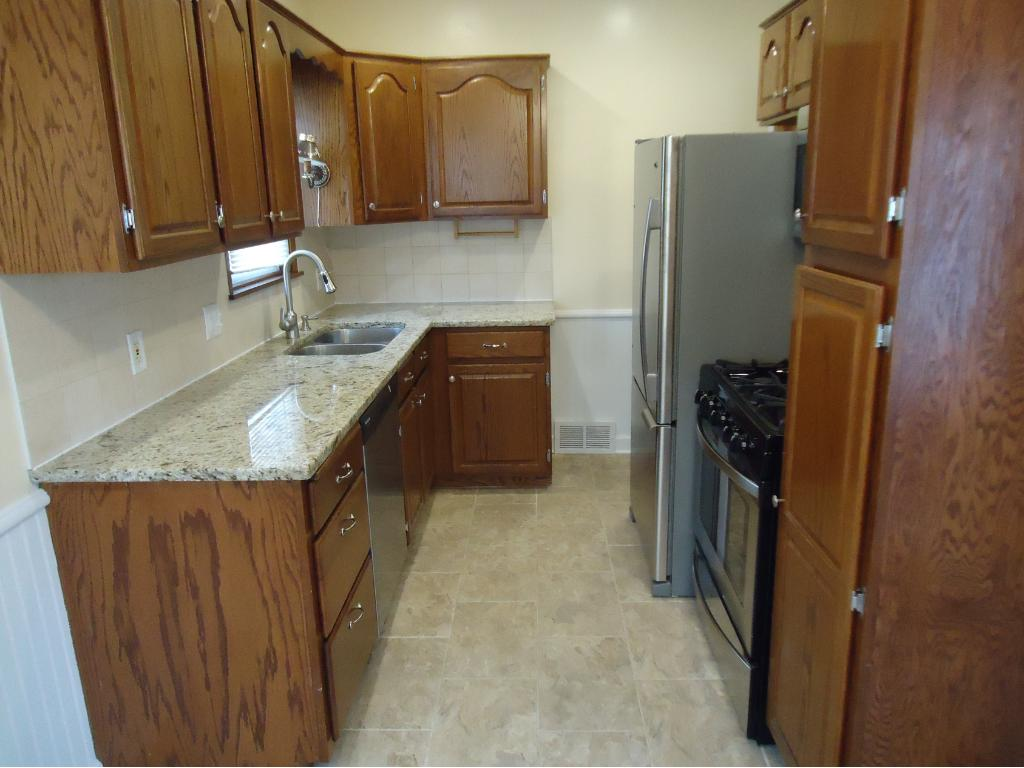 VIEW OF THE NEW STAINLESS STEEL AMANA REFRIGERATOR, KENMORE GAS RANGE, LG MICROWAVE AND FRIGIDAIRE DISHWASHER.