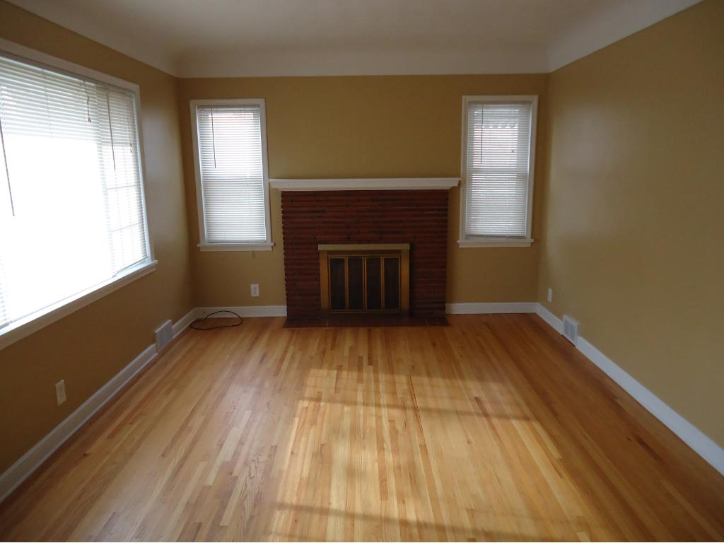 THE LIVING ROOM HAS A BEAUTIFUL BRICK FIREPLACE, COVE CEILING, HARDWOOD FLOOR AND COAT CLOSET.