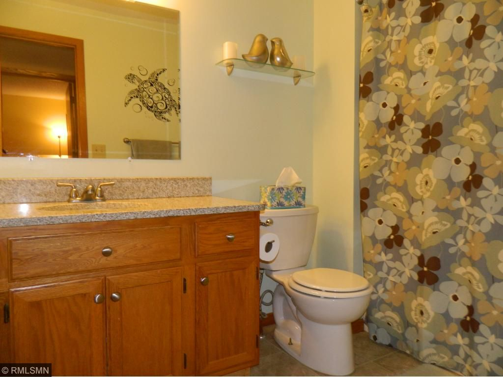 Granite countertops and updated flooring in remodeled bath.