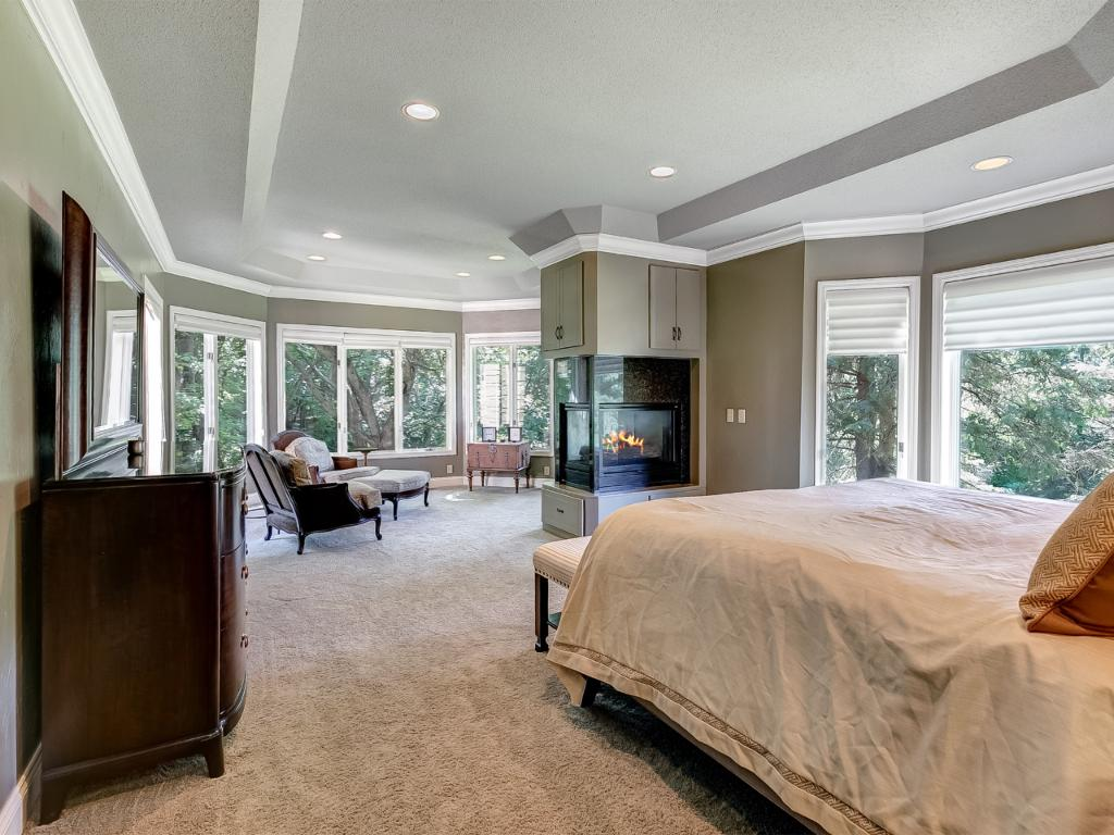 Main floor master suite with gas fireplace and woodland views.