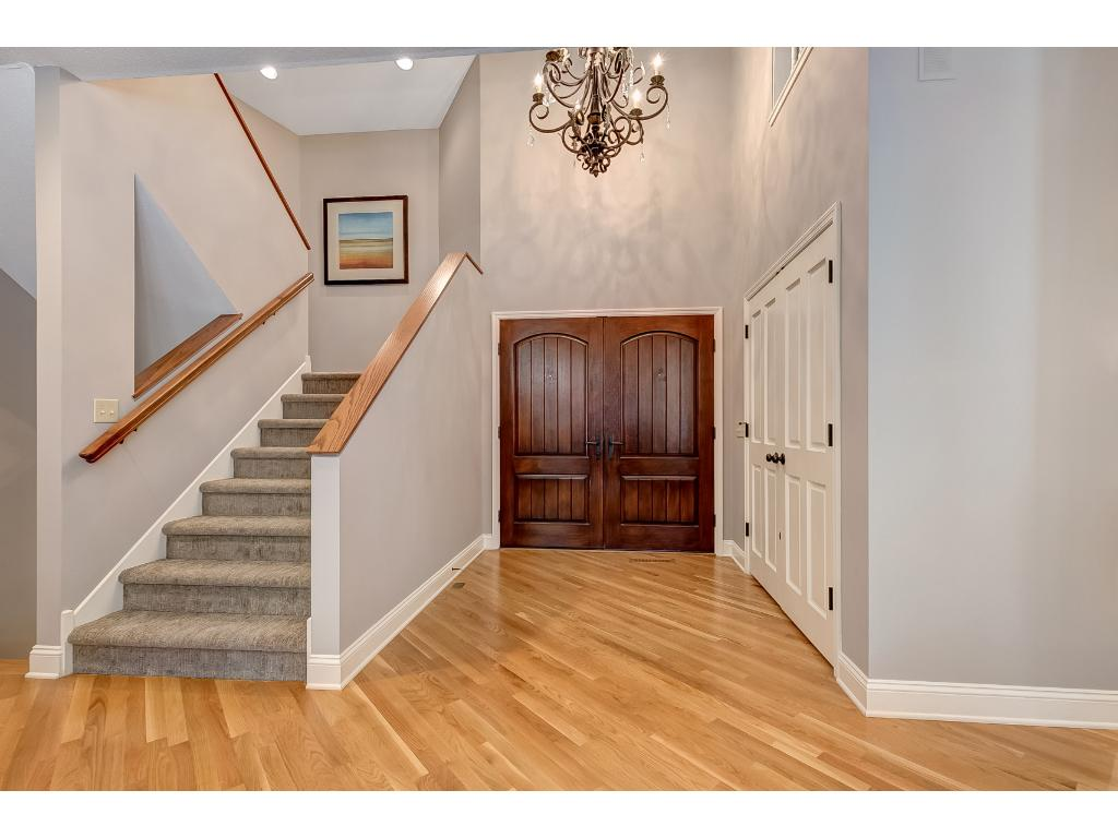 You are greeted by the grand 2-story vaulted living room as you enter the home.