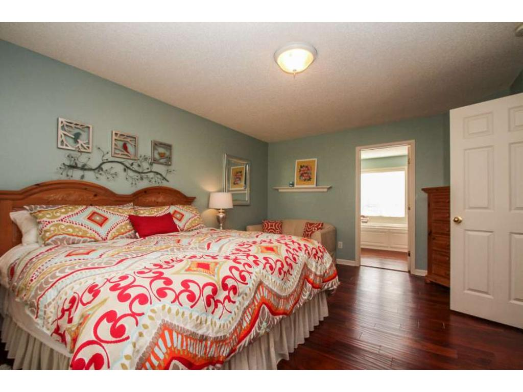 """Luxurious owner's suite with private full bath and oversized walk-in closet. Beautiful 5"""" hand scraped wood floors."""