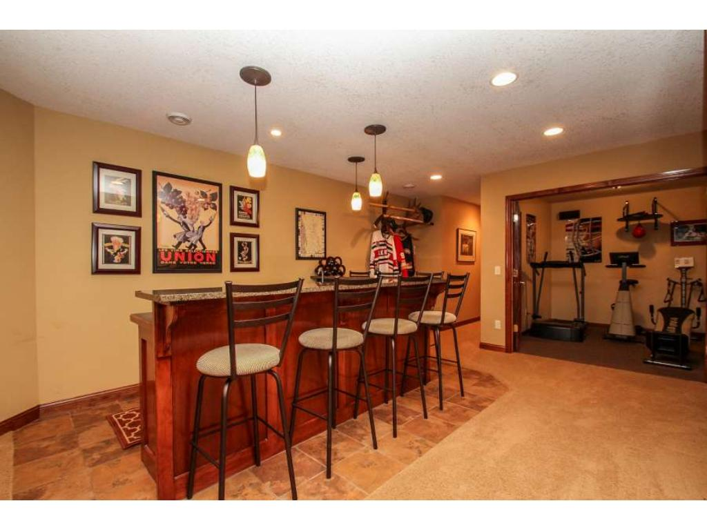 Wet bar with elegant pendant and recessed lighting, tile floor, under the counter refrigeratorand seating for up to 6.