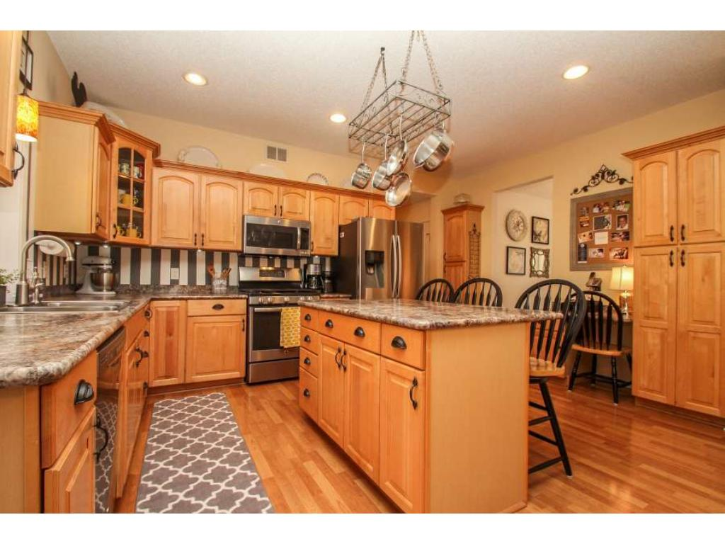 Grand, open kitchen features center island with seating, abundant, custom maple cabinetry and new stainless steel appliances. Check out the spacious pantry. Sure to please the family cook!