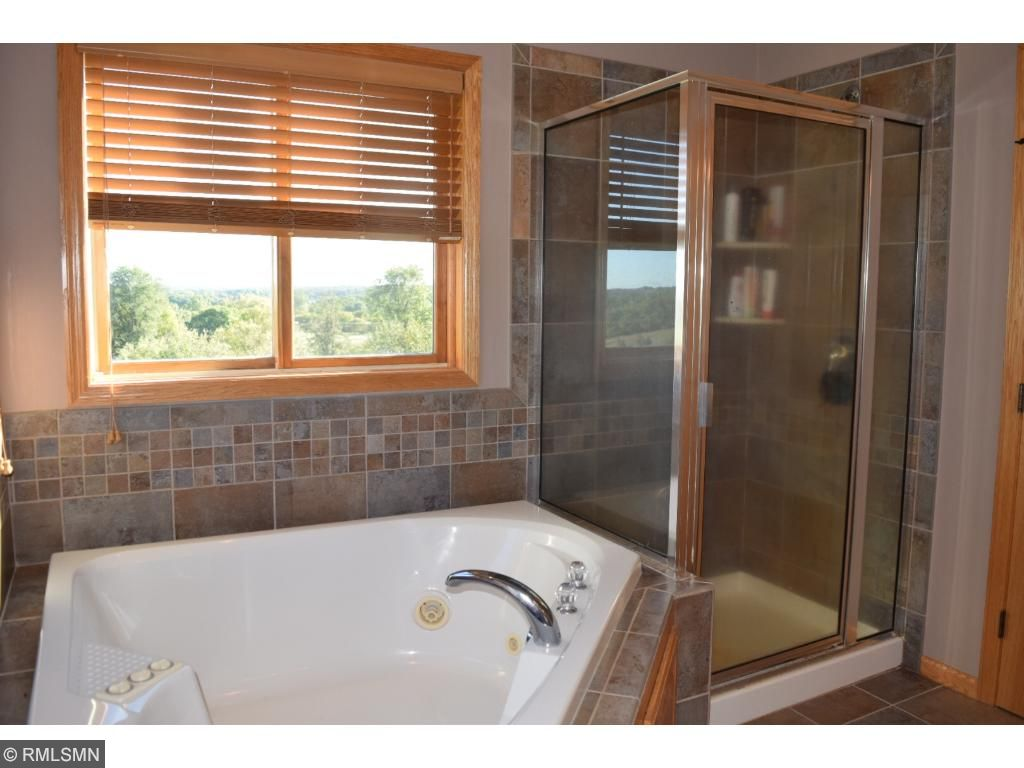 Luxurious Owner's Bath also enjoys corner whirlpool tub & glass front shower.