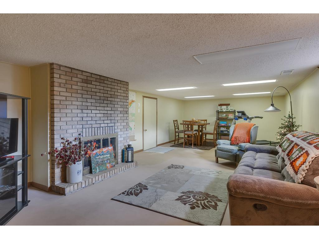 Lower level family room is cozy with another brick fireplace.