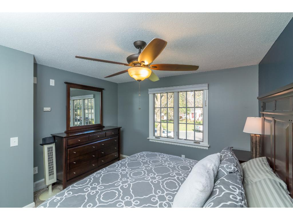 The master bedroom on the upper floor - complete with large windows, a nook for dressers, sizable closet space, and plush carpet. It's fitted with wall outlets for mounting a TV, and don't miss the light switches for lights in all bedroom closets!