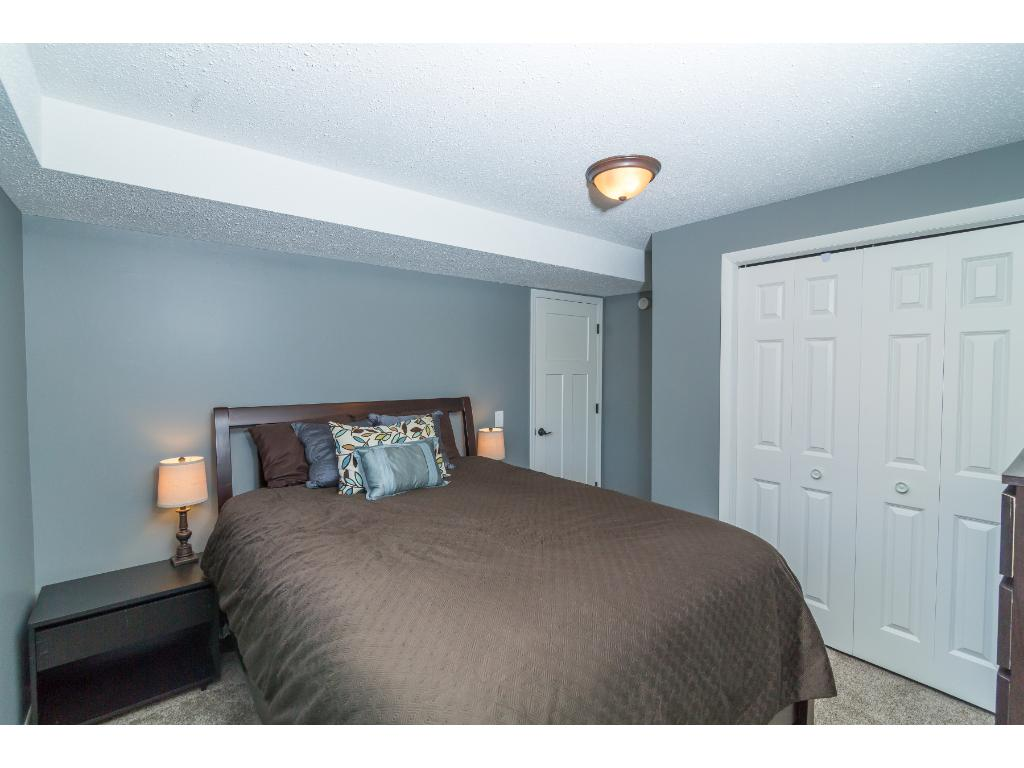 Bedroom 4 on the lower level -  Has large egress windows and the nice carpet the rest of the home has. This also contains the electrical panel. Don't miss the light switches for lighting in all bedroom closets!