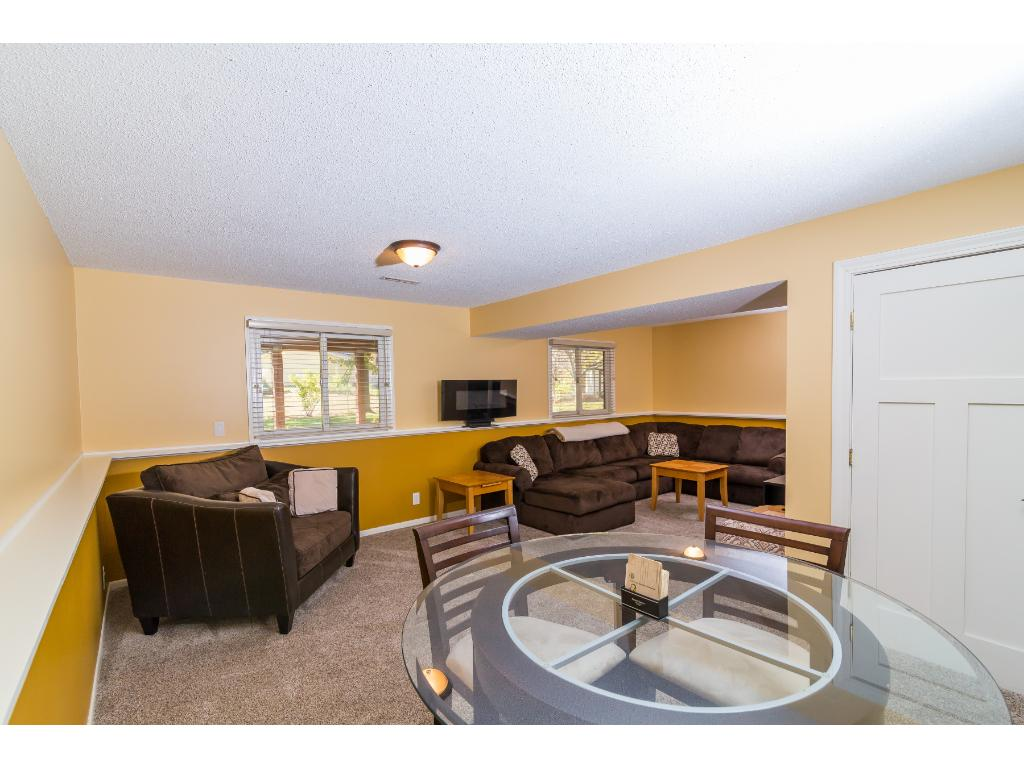 The lower level living area has plenty of room for whatever you'd prefer and dimmer switches to fit your mood. The L-shape is perfect for a poker table, TV nook, or whatever you'd like. Large windows lookout into the back yard.