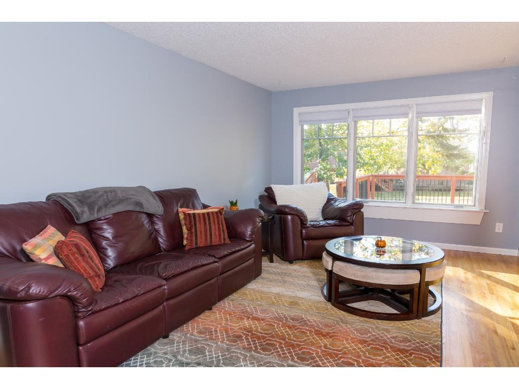 The modern color scheme, hardwood floors, white trim, and flowing floor plan make this living area feel great.